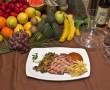 Plato de churrasco preparado a la brasa acompañado de patatas fritas, variedad de verduras y salsa de tomate