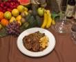 Plato de rabo de toro acompañado de patatas fritas y variedad de verduras